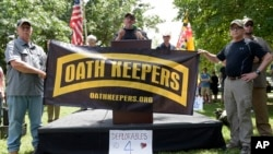 FILE - Stewart Rhodes, founder of the citizen militia group known as the Oath Keepers, center, speaks during a rally outside the White House in Washington, June 25, 2017. (AP Photo/Susan Walsh)