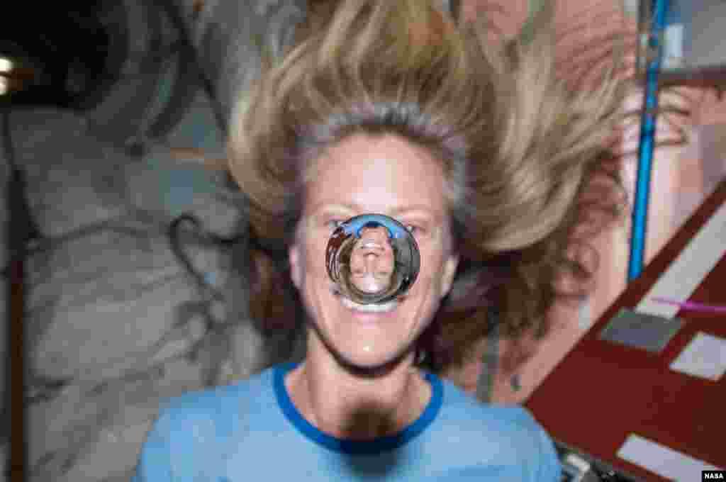 Wajah astronot NASA Karen Nyberg tampak tercermin pada tetesan air yang melayang di depannya.