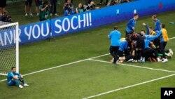 Les joueurs croates, à droite, jubilent après le tirs au but de la victoire, laissant le gardien de but russe Igor Akinfeev, à gauche, sans mots, lors du match de quart de finale opposant la Russie et la Croatie à la Coupe du monde 2018 au stade Fisht de