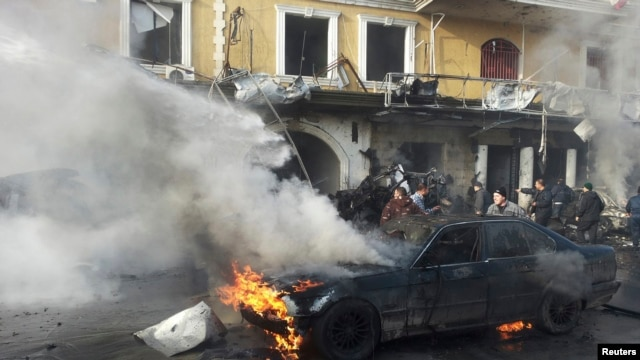 People gather near a burning car at the site of an explosion in the Shi'ite town of Hermel, Jan. 16, 2014.