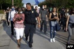 """El jefe de policía de Houston, Art Acevedo, camina del brazo de una mujer afroestadounidense durante un evento en se reclamó """"Justicia para George Floyd"""" en Houston, Texas, el 30 de mayo de 2020."""