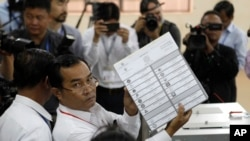 A polling station officer shows a ballot before voting began in the country's general election, at a polling station in Takhmua in Kandal province, southeast of Phnom Penh, Cambodia, July 29, 2018.