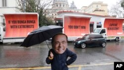 An actor wearing a mask depicting former Italian premier Silvio Berlusconi performs alongside billboards March 5, 2018, in Rome. The billboards were organised by the global civic movement Avaaz as a reaction to the right-wing coalition not reaching a majo