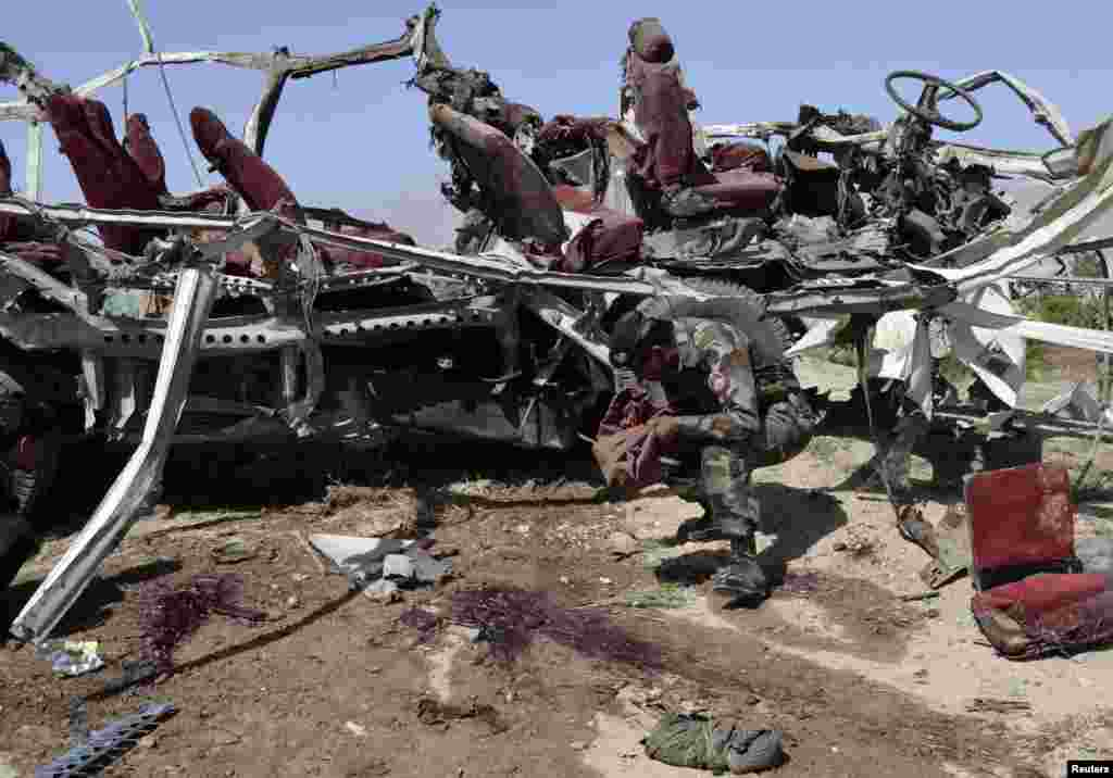 A security official collects evidence near the remains of a damaged vehicle at the site of a bomb blast in Quetta, Pakistan, May 23, 2013.