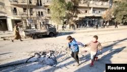 小男孩们在叙利亚亲政府军队空袭后的地区旁玩耍(2016年2月8日)。.