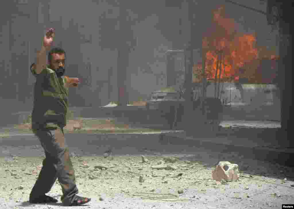 A man points towards a burning car, caused by what activists said was shelling by forces loyal to Syria's President Bashar al-Assad, Damascus, July 23, 2013.