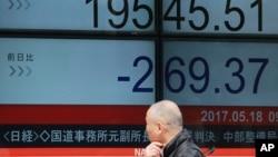 ຊາຍຄົນນຶ່ງ ແນມເບິ່ງ ແຜ່ນຈໍອີເລັກໂທຣນິກ ຂອງລາຄາຮຸ້ນຕ່າງໆ ຢູ່ທີ່ຕະຫຼາດຮຸ້ນ Nikkei ຂອງຍີ່ປຸ່ນ ທີ່ສະແດງໃຫ້ເຫັນດັດຊະນີຂອງ 225 ບໍລິສັດຊື້ຂາຍຮຸ້ນ, ວັນທີ 18 ພຶດສະພາ 2017, ໃນນະຄອນຫຼວງໂຕກຽວ.
