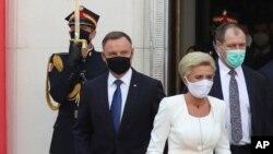Presiden konservatif Polandia Andrzej Duda (kiri) dan Ibu Negara Agata Kornhauser-Duda, meninggalkan gedung parlemen usai upacara pengambilan sumpah Duda untuk masa jabatan lima tahun kedua di Warsawa, Polandia, 6 Agustus 2020.