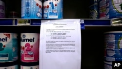 A notice warns customers of precautionary recall of products in a supermarkert of Lille, northern France, Monday, Dec. 11, 2017. Baby milk maker Lactalis and French authorities have ordered a global recall of millions of products over fears of salmonella bacteria contamination. The French company, one of the largest dairy groups in the world, said it has been warned by health authorities in France that 26 infants have become sick since Dec. 1. (AP Photo/Michel Spingler)
