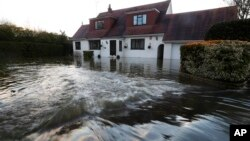 Water overflowing from the River Thames floods a house at Wraysbury, England, Feb. 10, 2014.