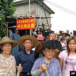 """月塘村民聚集在自搭的""""维权棚""""前"""