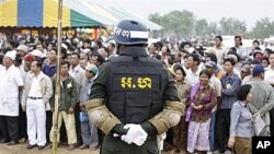 A Cambodian military policeman stands watch during the ground breaking ceremony of a Chinese funded road at Koun Damrey village, Banteay Meanchey province, about 15 kilometers (9 miles) east of Cambodia's border with Thailand, February 15, 2011.