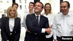 "France's President Emmanuel Macron and his wife Brigitte speak with French entrepreneur and businessman Xavier Niel, right, during the inauguration of start-ups incubator ""Station F,"" in Paris, France, June 29, 2017."
