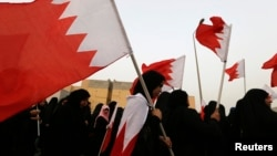 FILE - Opposition protesters, holding Bahraini flags, are seen during an anti-government rally in Sitra, south of Manama, June 28, 2013.