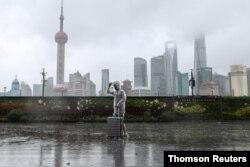 """颱風""""煙花""""正在逼近上海,一位男子冒雨走在黃浦江邊的外灘。 (路透社照片)"""