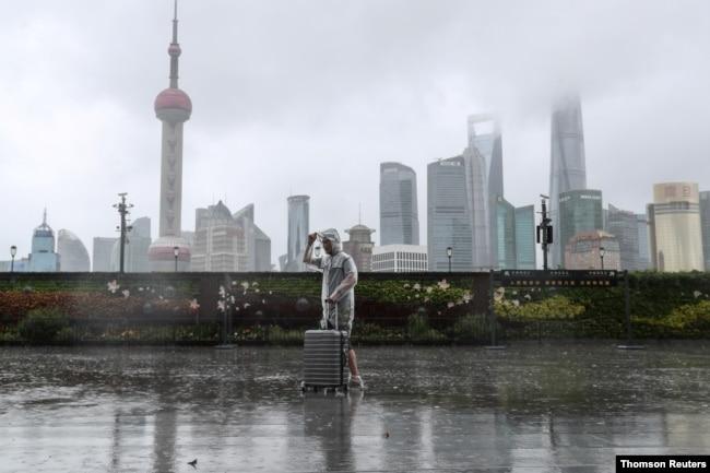 """台风""""烟花""""正在逼近上海,一位男子冒雨走在黄浦江边的外滩。(路透社照片)"""