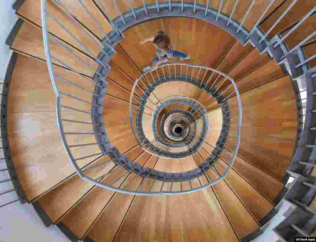A woman walks down a spiral staircase at Gottesaue castle in Karlsruhe, Germany.
