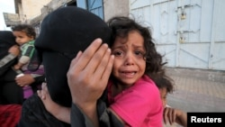 FILE - A girl cries next to her mother covering her face as they flee from an airstrike on an army weapons depot in Yemen's capital Sanaa.