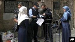 Polisi Israel memeriksa dokumen dua perempuan Palestina yang akan memasuki komplek kota tua Yerusalem, Kamis (8/10).