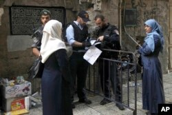 FILE - Israeli police check the papers of a Palestinian woman in Jerusalem's Old City, Oct. 8, 2015.