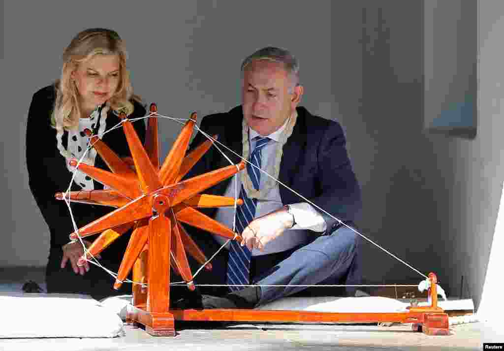 Israeli Prime Minister Benjamin Netanyahu spins cotton on a wheel as his wife Sara looks on during their visit to Gandhi Ashram in Ahmedabad, India.