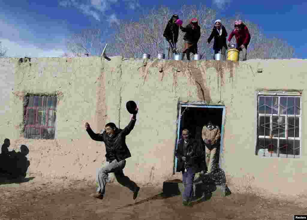 Tadjik women throw water on men from rooftop as they take part in a celebration to welcome the coming spring in Tadjik autonomous county, Kashgar, Xinjiang Uighur Autonomous Region, China, March 18, 2015.