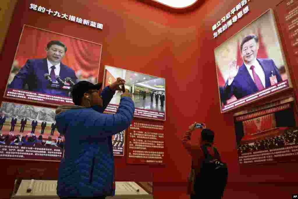 """2018年11月15日,北京中国国家博物馆举办中国改革开放40周年展览突出习近平主席,参观者用手机拍照。有大字标题说""""确立习近平新时代中国特色社会主义思想为党的指导思想""""。香港《南华早报》11月22日报道,《陕西日报》内部文件显示,该报两名编辑在这16个字的""""习近平思想""""提法上外加了""""总书记""""三个字,被定性为""""重大差错"""",从而分别被罚款人民币1万元与5千元。"""