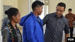 Mendikbud Anies Baswedan (kanan) memakaikan jaket untuk salahsatu guru yang akan mengajar di kabupaten Puncak propinsi Papua, Minggu (24/5). (VOA/Munarsih Sahana)
