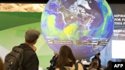 People look at an Earth globe display at the COP21, the United Nations conference on climate change in Le Bourget, Dec. 10, 2015.