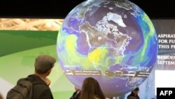 FILE - People watch the Earth globe at the COP21, the United Nations conference on climate change in Le Bourget, Dec. 10, 2015.