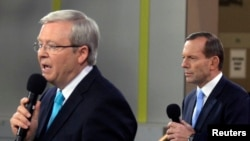 Opposition leader Tony Abbott (R) listens to Australian Prime Minister Kevin Rudd during the People's Forum in Sydney, Aug. 28, 2013.
