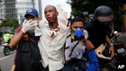 Des paramédicaux portent secours à un homme blessé lors des affrontements entre manifestants et forces de l'ordre à Caracas, Venezuela, le 20 avril 2017.