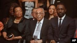 FILE - UMnu. Ahmed Kathrada, center, umkaNelson Mandela, UGracia Machel lomlingisa uMnu. Idris Elba, babukele umdlalo omayelana loMandela.