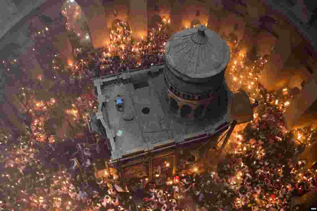អ្នកកាន់សាសនាគ្រិស្តធ្វើការបួងសួងនៅផ្នូររបស់ព្រះយេស៊ូ នៅពេលបាតុភូតនៃភ្លើងពិសិដ្ឋបានកើតឡើងនៅក្នុងព្រះវិហារ Holy Sepulchre ក្នុងក្រុងហ្ស៊េរុយសាឡិម ប្រទេសអ៊ីស្រាអែល កាលពីថ្ងៃទី៣០ ខែមេសា ឆ្នាំ២០១៦។