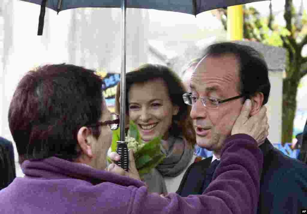 El candidato socialista y vencedor de las elecciones en Francia, Francois Hollande y su comañera, Valerie Trierweiler, son saludados por votantes. (AP)