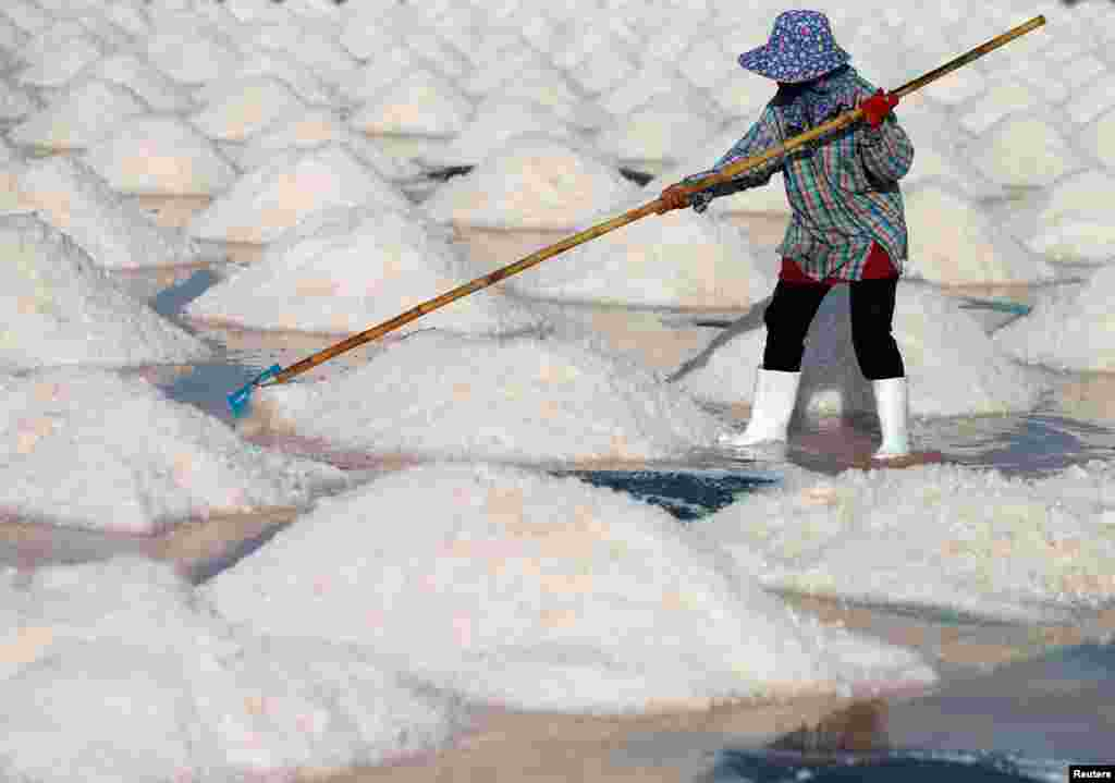 A woman works on a salt farm in Phetchaburi, Thailand, May 9, 2020.