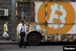 FILE - People walk past a board with the logo of Bitcoin in a street in Yerevan, Armenia September 9, 2019. REUTERS/Anton Vaganov