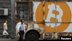 FILE - People walk past a board with the logo of Bitcoin in a street in Yerevan, Armenia September 9, 2019. (REUTERS/Anton Vaganov)