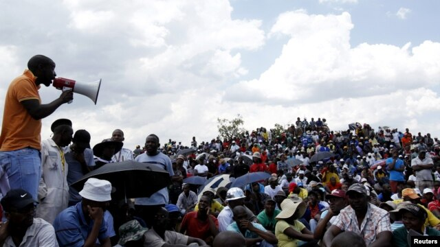 Striking miners listen to an address by their leader at the AngloGold Ashanti mine in Carletonville, northwest of Johannesburg, October 19, 2012.