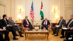 U.S. Secretary of State John Kerry, center left, sits with Palestinian President Mahmoud Abbas, during their talks in Paris, France, Feb. 19, 2014.