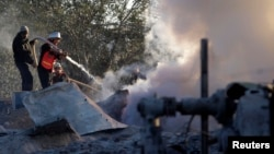 A member of Palestinian civil defense extinguishes a fire at a Hamas training camp after it was hit by an Israeli air strike in Khan Younis in the southern Gaza Strip, Dec. 24, 2013.