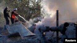 Đội dân vệ Palestine dập tắt lửa tại một trại huấn luyện của nhóm Hamas sau khi nơi này bị máy bay Israel oanh kích, 24/12/13