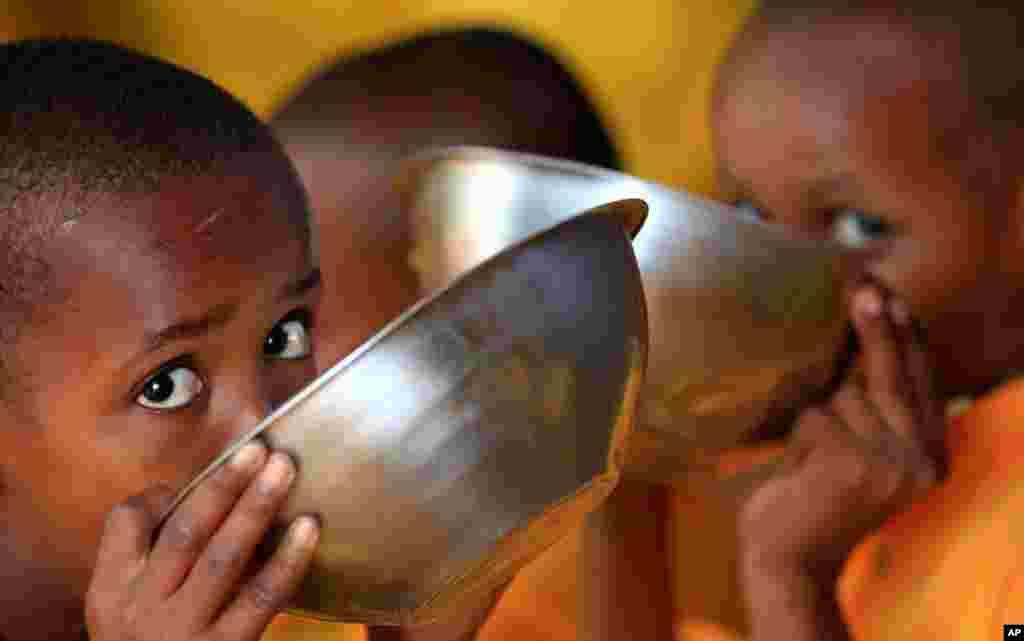 (8月2日)索马里小难民在肯尼亚-索马里边境附近的达达阿布难民营内的利班综合学校课间休息期间喝粥充饥。