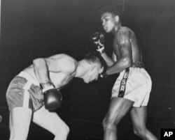 In this Oct. 29, 1960 file photo, Cassius Clay, in white trunks, is shown in his professional boxing debut, in Louisville's Freedom Hall against Tunney Hunsaker.
