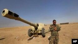 Seorang laskar peshmerga Kurdi berdiri di samping senjata api di Mahmoudiyah, Irak. (Foto: dok.)