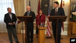 Latvian President Raimonds Vejonis (right) looks at US Sen. John McCain, (center left) during a press conference, Dec. 28, 2016, in Riga, Latvia, while Lindsey Graham, R-SC., and Amy Klobuchar, D-Minn., stand in the background.