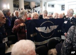 FILE - Members of the Women Airforce Service Pilots (WASP) hold up a flag on Capitol Hill in Washington after the ceremony where the first women in to fly America's military aircraft were awarded the Congressional Gold Medal, March 10, 2010.