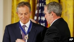 FILE - President George W. Bush presents the Presidential Medal of Freedom to former British prime minister Tony Blair, Jan. 13, 2009, during a ceremony at White House in Washington.