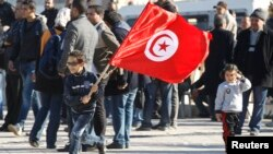 A Tunisian boy waves a flag during a rally in Tunis on December 17, 2013, marking the third anniversary of the Tunisian revolution.