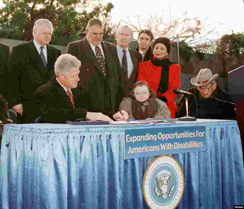 Then President Bill Clinton signs new disabilities legislation at the FDR memorial Dec. 17, 1999 that could allow as many as eight million disabled Americans to go to work without fear of losing their federal health insurance.